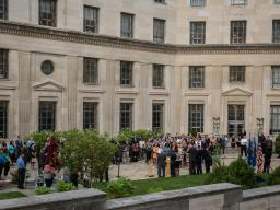 Employees participate in a moment of silence as part of a commemoration ceremony with Department of Justice