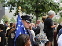 A police officer holds the American flag during the 15th anniversary ceremony at the National September 11 Memorial Plaza