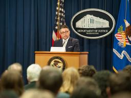 Makan Delrahim speaking at a podium in front of an audience of event attendees.