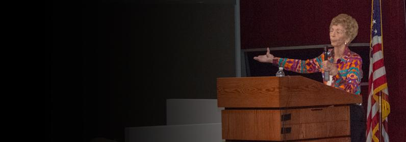 Anne K. Bingaman speaking at a podium with the American flag next to her
