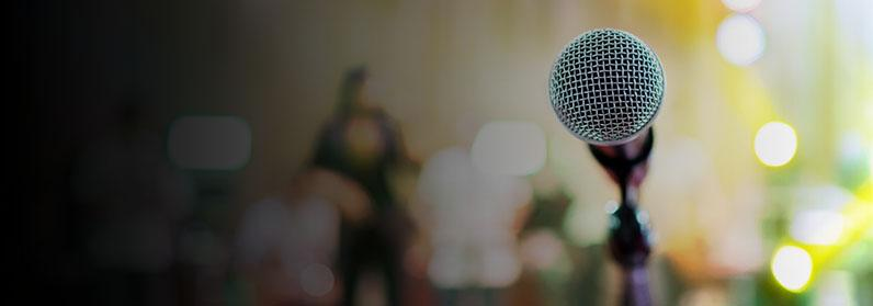 Decorative photo of microphone with a band blurred in the background