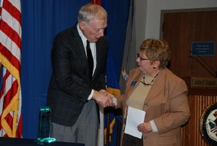 Acting U.S. Attorney Tom Larson presents the Crystal Kipper & Ali Kemp Memorial Award to Syngergy Services.
