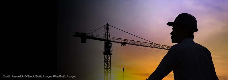 Portrait of architect silhouette wearing a helmet at construction site with crane background and sunset. Credit: lersan8910/iStock/Getty Images Plus/Getty Images