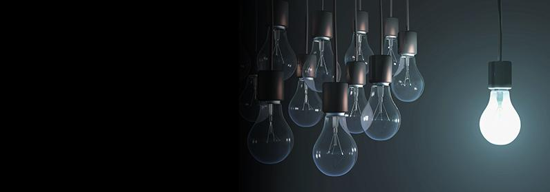One lit bulb hangs in front of a group of unlit bulbs (Credit: Thinkstock/Getty Images)