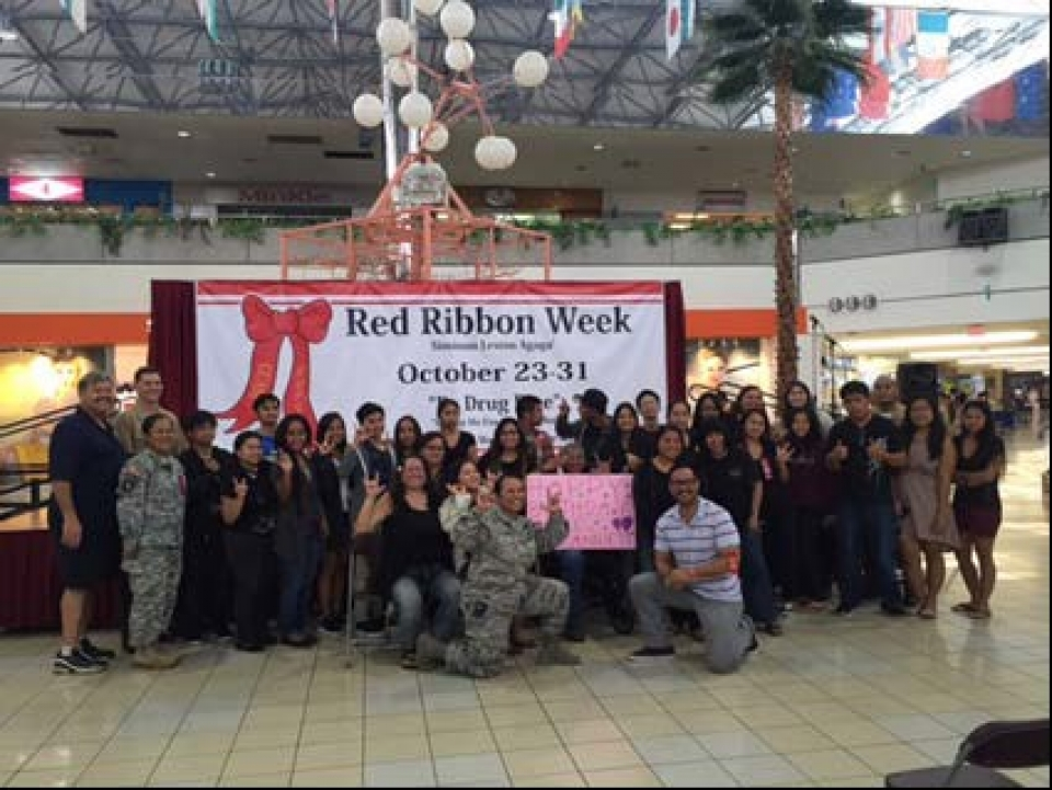 Picture of Members of the Red Ribbon Committee with students of the Guam Community College's sign language class who performed several numbers at the Red Ribbon Campaign Outreach at the Micronesia Mall in Guam