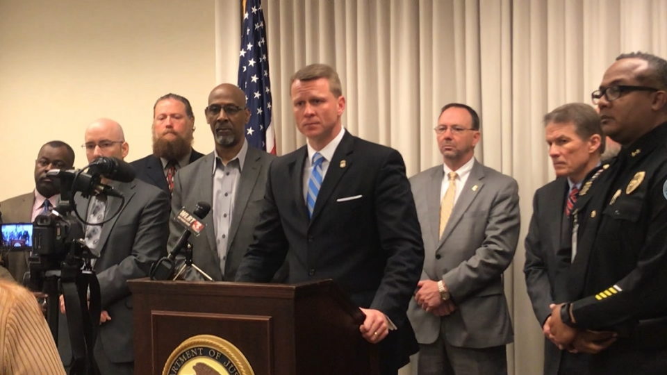 U.S. Attorney Mike Hurst stands at the podium surrounded by local and federal law enforcement leaders to announce the Fugitive Task Force arrests in Jackson, Mississippi