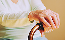 Elderly woman's hands on cane