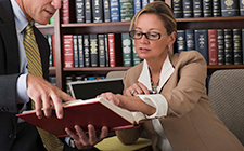 Female lawyer pointing to statutes in a book