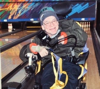 Thomas Graziani at a bowling alley, smiling, wearing a jacket and a beanie while in a wheelchair..