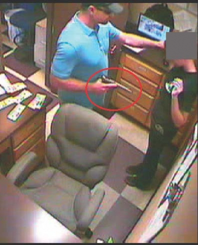 Jones holds a victim's arm while conducting an armed robbery at the Purple Parrot in Medford.