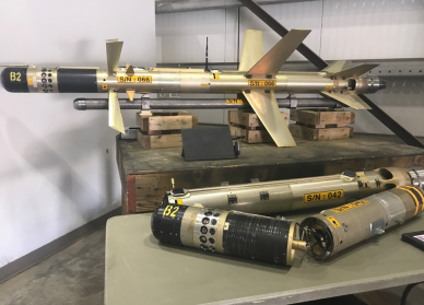 Two black and tan surface to air missiles that were part of the seizure. One is one display on top of a wooden box and the other is in parts on a different box.