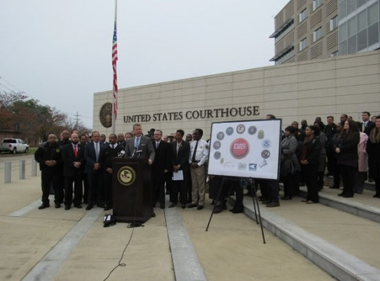 U.S. Attorney Mike Hurst standing at the podium next to a sign showing the Project Eject graphic surrounded by various local, state, and federal law enforcement seals. Behind U.S. Attorney Hurst are local, state, and federal law enforcement officials and supporters.