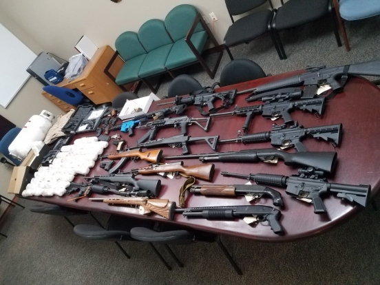 Over 30 firearms and a large quantity of meth laid out across a conference table.
