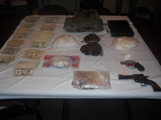 Guns, drugs, and cash found in the residence.