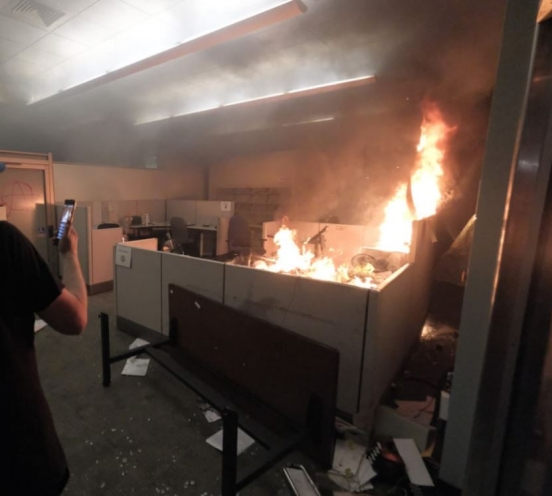 A demonstrator photographs the fire in the Corrections Records Office on May 29, 2020