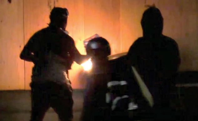 Photograph depicting Streeter-Hillerich attempting to ignite a fire on a dumpster pushed against the plywood affixed to the Portland Police Bureau's North Precinct.