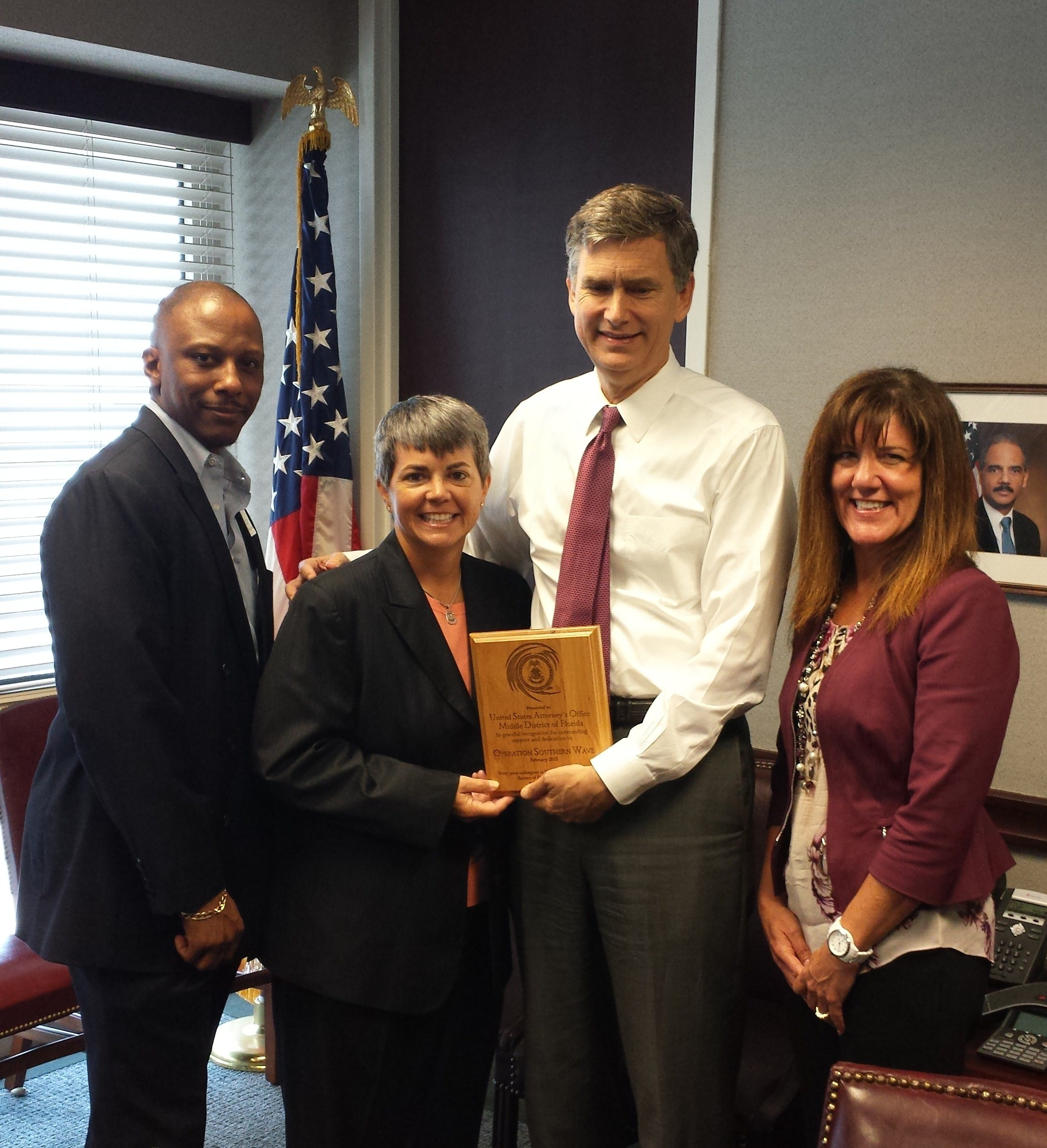 U.S. Attorney Lee Bentley is presented with an award