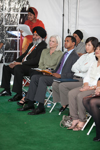 Jasdeep Malhi (standing), Harpreet Singh, U.S. Attorney Melinda Haag, Associate Director of White House Office of Public Engagement D. Paul Monteiro, joined by others.