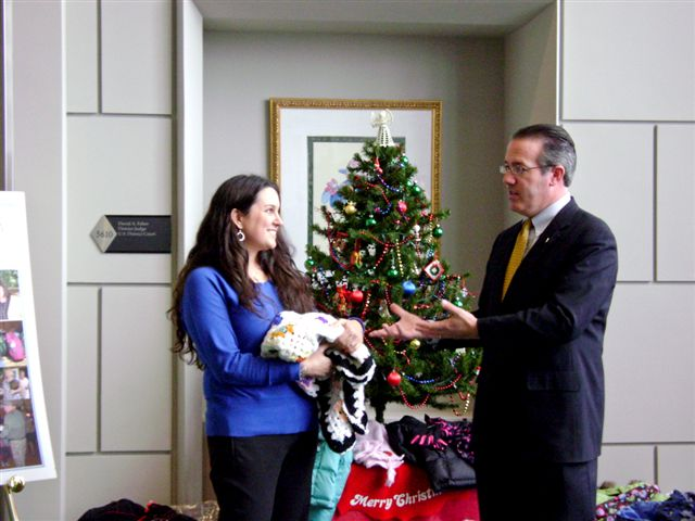 U.S. Attorney Booth Goodwin presents items to Carrie Robey of Mission West Virginia during a holiday luncheon at the Robert C. Byrd Courthouse in Charleston